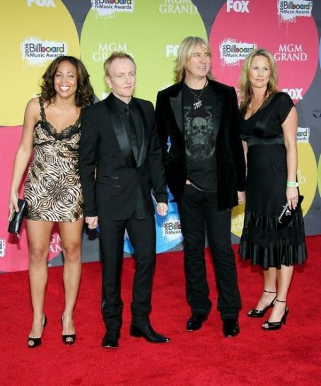 Kristine Elliott Musician Phil Collen (2nd from left) with wife Anita (L), Joe Elliott (2nd from right) with wife Kristine arrive at the 2006 Billboard Music Awards at the MGM Grand Garden Arena December 4, 2006 in Las Vegas, Nevada.
